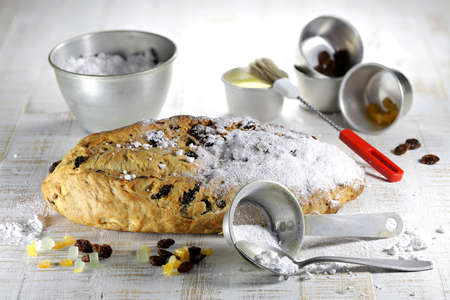 freshly baked traditional Saxon Christmas Stollen with some baking ingredients to be finished with powdered sugar Archivio Fotografico