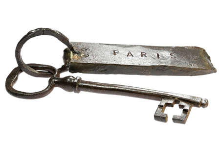 vintage hand-forged key with fob 'PARIS' isolated on white background