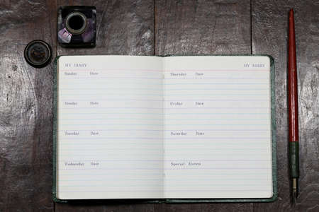 Opened blank diary with dib pen and inkwell on wooden table