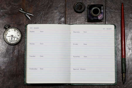 opened blank diary with dib pen and inkwell on desktop