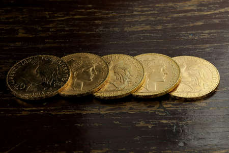 French 20 Francs gold coins on rustic wooden background