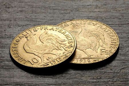 French 10 and 20 Francs gold coins (reverse with rooster) on rustic wooden background