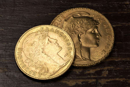 French 10 and 20 Francs gold coins (obverse with Marianne) on rustic wooden background