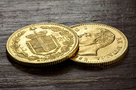 Italian 20 Lira gold coins on rustic wooden background