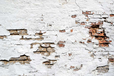 weathered brick wall with crumbling white plaster for background use
