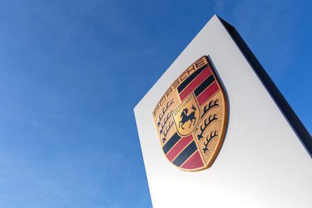 Porsche dealership sign against blue sky