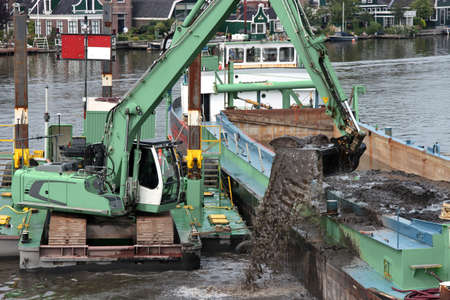 crawler excavator on floating pontoon deepening the fairway on a river