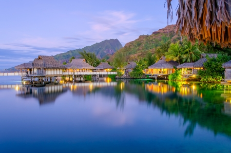 Overwater Bungalows at dusk, French Polynesia Stock Photo