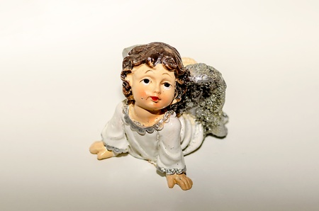 Ceramic Statuette of an Inspired Cute Angel, isolated on white photo