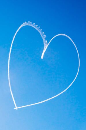 Romantic heart written in the blue sky by a small aircraft photo