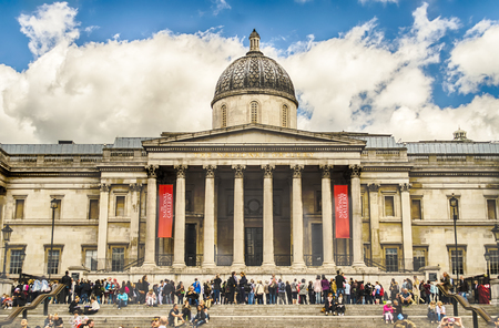 typically english: LONDON - MAY 28: Tourists in Trafalgar Square outside the National Gallery, May 28, 2015 in London. Founded in 1824, the National Gallery is one of the most visited museum in the world