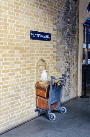 quarters: LONDON - MAY 31: Kings Cross station wall visited by fans of Harry Potter to photograph sign for platform nine and three quarters with trolley, London, May 31, 2015.