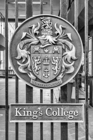LONDON - MAY 31: Emblem on the entrance gate of Kings College in London, May 31, 2015. Kings College is regarded as one of the leading multidisciplinary research universities in the world