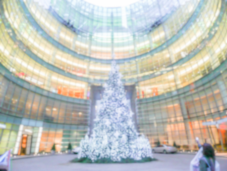 intentionally: Defocused background of a shopping mall with Christmas Tree. Intentionally blurred post production for bokeh effect Stock Photo
