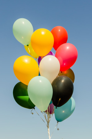 helium: Colorful bunch of helium balloons isolated on background