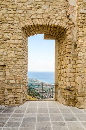 Oud venster uit de ruïnes van een oud kasteel met prachtig uitzicht over de zee