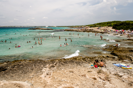 4 people: GALLIPOLI, ITALY - AUGUST 4: People enjoying a beautiful day at the beach in Punta della Suina near Gallipoli, Apulia, Italy, August 4, 2015.