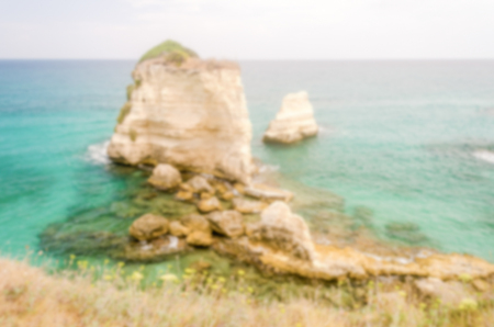 intentionally: Defocused background with scenic rocky cliffs in Salento, Italy. Intentionally blurred post production for bokeh effect Stock Photo