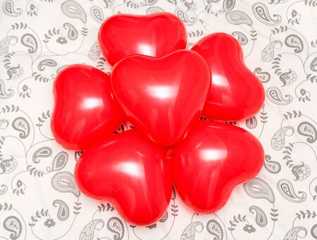 romanticism: Composition of red heart shaped balloons on a blanket. Concept for romanticism Stock Photo
