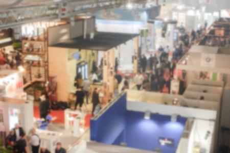 Onscherpe achtergrond van een beurs met mensen een bezoek aan de commerciële tentoonstelling. Opzettelijk wazig postproductie voor bokeh-effect
