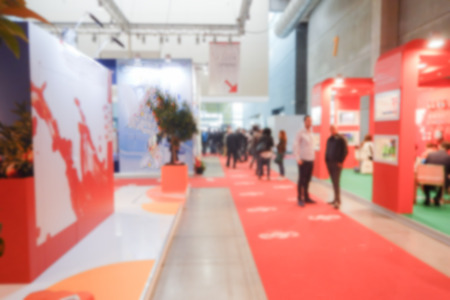 Defocused background of a trade show with people visiting the commercial exhibition. Intentionally blurred post production for bokeh effect Фото со стока - 58923717