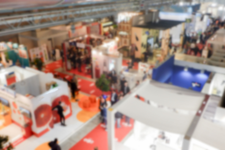 intentionally: Defocused background of a trade show with people visiting the commercial exhibition. Intentionally blurred post production for bokeh effect