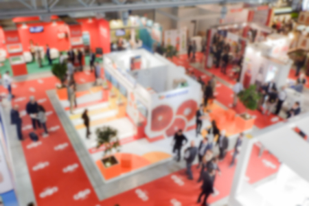 Defocused background of a trade show with people visiting the commercial exhibition. Intentionally blurred post production for bokeh effect