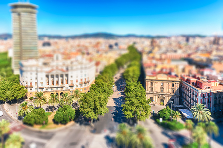 Scenic aerial view of La Rambla, tree-lined pedestrian mall and popular tourist sight in Barcelona, Catalonia, Spain. Tilt-shift effect applied