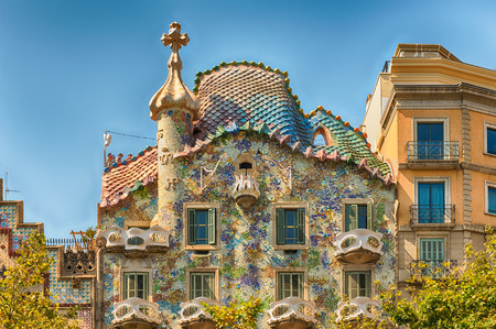 BARCELONA - AUGUST 9: Facade and Dragons tile rooftop of Casa Batllo, renowned building designed by Antoni Gaudi and iconic landmark in Barcelona, Catalonia, Spain, on August 9, 2017 Редакционное