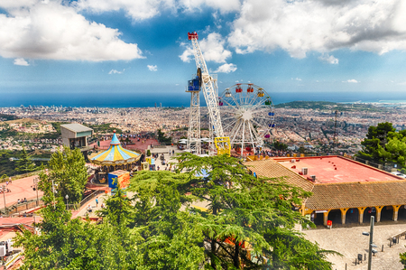 BARCELONA - AUGUST 12: View over the Tibidabo Amusement Park and Barcelona, Catalonia, Spain on August 12, 2017. The park opened in 1905 and is among the oldest in the world still functioning