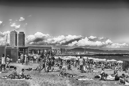 BARCELONA - AUGUST 10: People enjoying a sunny day on La Barceloneta beach, Barcelona, Catalonia, Spain, on August 10, 2017