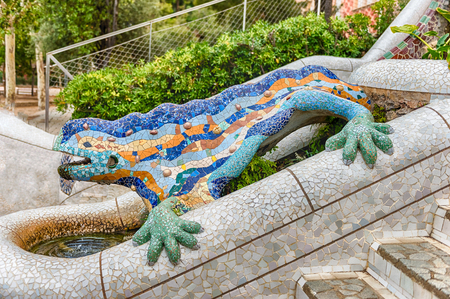 Multicolored sculpture with mosaic salamander or lizard, also known as El Drac (Dragon in english). The fountain is the most iconic landmark in Park Guell, Barcelona, Catalonia, Spain