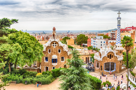 BARCELONA - AUGUST 9: Gingerbread houses, modernist buildings at the entrance of Park Guell in Barcelona, Catalonia, Spain, on August 9, 2017.  Designed by Antoni Gaudi, the park opened in 1926