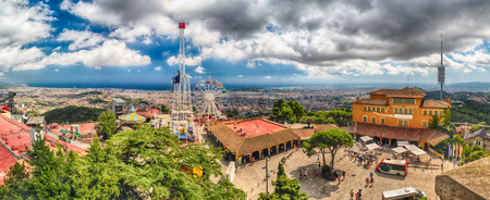BARCELONA - AUGUST 12: Panoramic view over Tibidabo Amusement Park and Barcelona, Catalonia, Spain on August 12, 2017. The park opened in 1905 and is among the oldest in the world still functioning