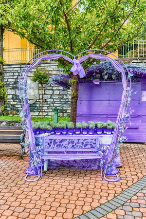 Scenic heart-shaped violet bench decorated with flowers and laces. Love concept Banque d'images