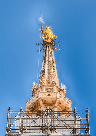 Golden Madonna statue, aka Madonnina, on the rooftop of the gothic Cathedral, the most iconic landmark of Milan, Italy
