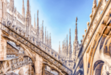 Defocused background with marble spiers and statues on the roof of the gothic Cathedral of Milan, Italy. Intentionally blurred post production for bokeh effect