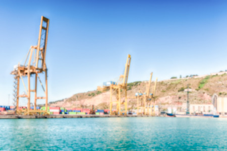 Defocused background of container cranes for loading and unloading container ships at the commercial port of Barcelona, Catalonia, Spain. Intentionally blurred post production for bokeh effect Banque d'images