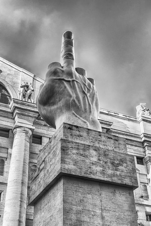 MILAN - SEPTEMBER 11: The controversial sculpture L.O.V.E. by the Italian artist Maurizio Cattelan, in front of the stock exchange building in Piazza Affari, Milan, Italy, September 11, 2017 Editorial