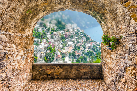 Scenic rock arch balcony with aerial view of Positano Village on the Amalfi Coast, Italy 免版税图像