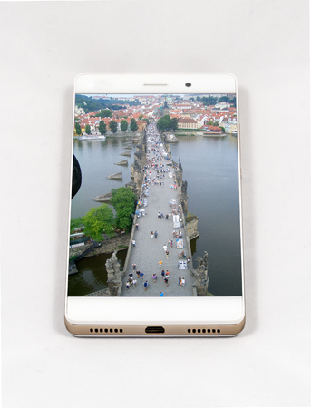 Modern smartphone with full screen picture of Charles Bridge and the Castle of Prague, Czech Republic. Concept for travel smartphone photography. All images in this composition are made by me and separately available on my portfolio Banco de Imagens