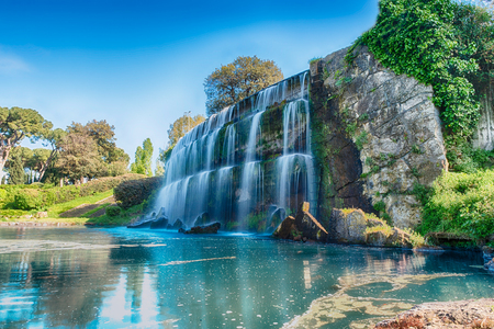 Long exposure with the scenic waterfall in the big fountain of EUR artificial lake, modern district in the south of Rome, Italy