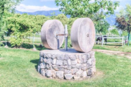 Defocused background with a millstone in the countryside. Intentionally blurred post production for bokeh effect Stock Photo