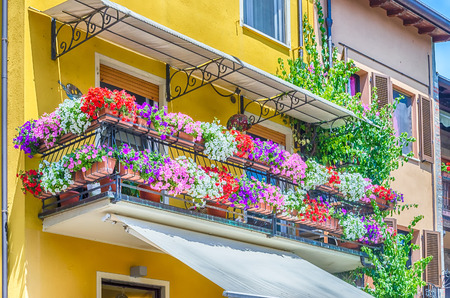 Picturesque balcony with flowers as seen in a small town in northern Italy