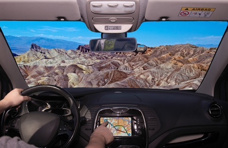 Driving a car while using the touch screen of a GPS navigation system towards Zabriskie Point, scenic place in Death Valley, California, USA Stockfoto