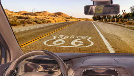 Looking through a car windshield with view of the Historic Route 66, with pavement sign in California, USA