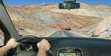 Driving a car in towards a isolated road among the rocks in Death Valley, California, USA