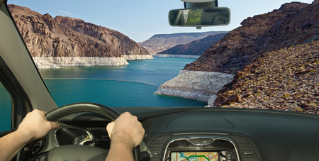 Driving a car with view of Colorado river in front of the Hoover Dam on the Nevada side, USA