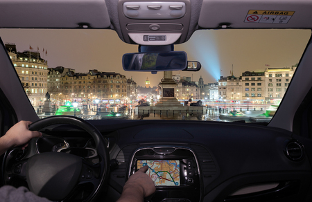 Driving a car while using the touch screen of a GPS navigation system towards Trafalgar Square at night with the Big Ben on the background, London, UK Stockfoto
