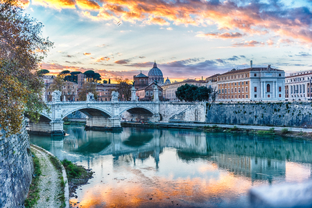 Beautiful sunset over the Tiber river and St. Peters Cathedral in Rome, Italy
